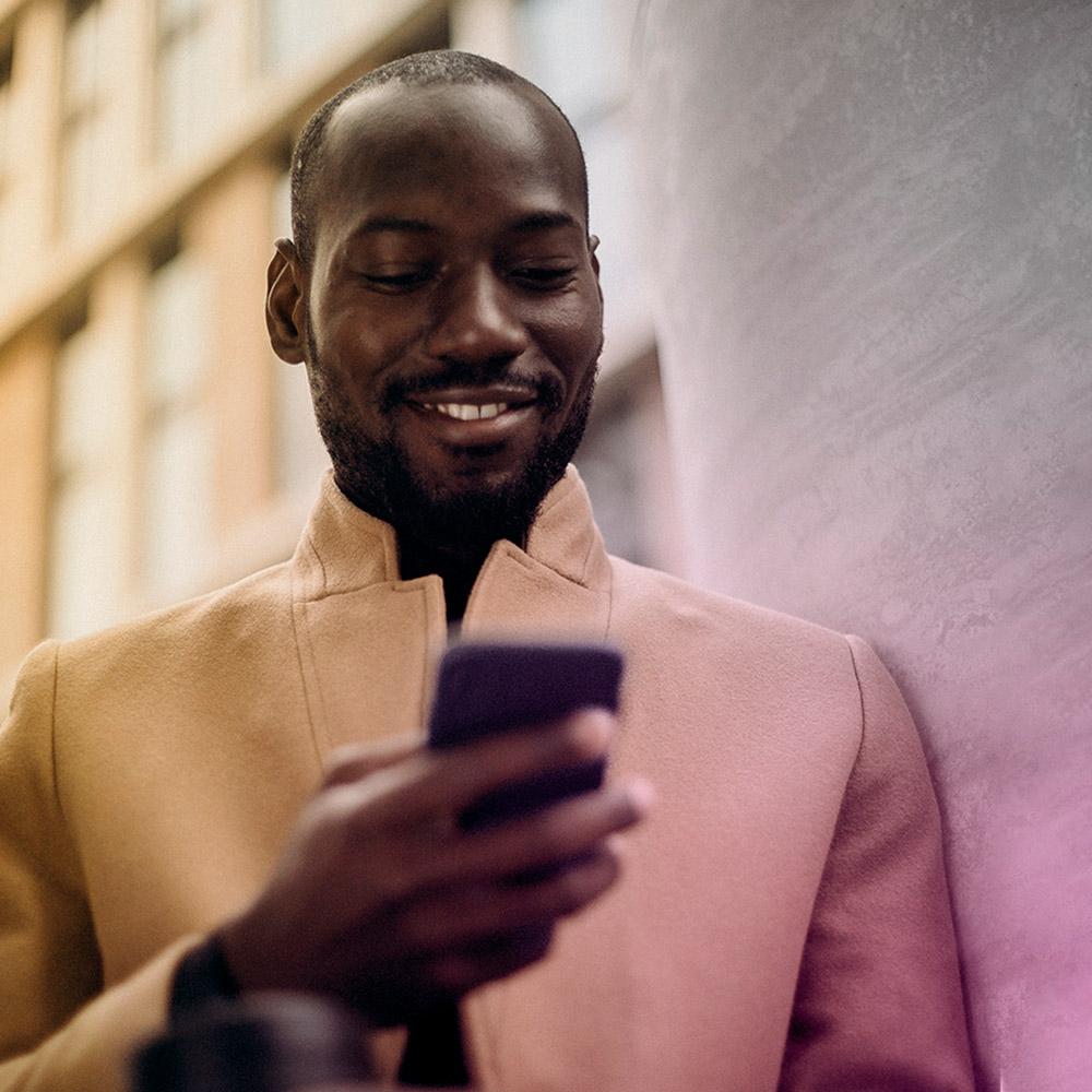 Retrato de um homem a sorrir enquanto usa o smartphone Y81