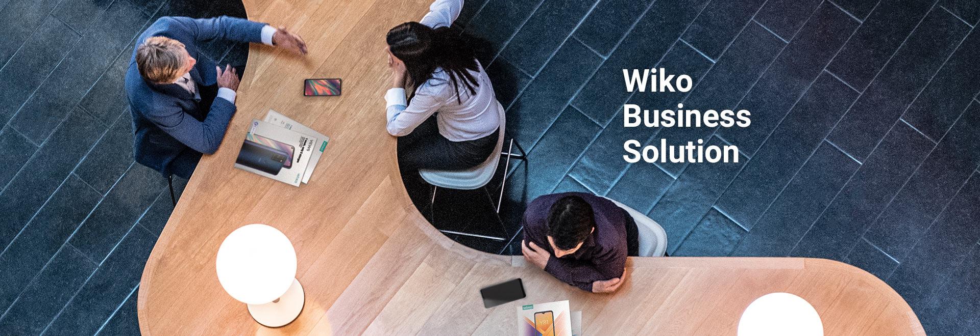 Vue de haut de personnes assises autour d'un bureau en bois représentant le W de Wiko - titre intégré : Wiko Business Solutions