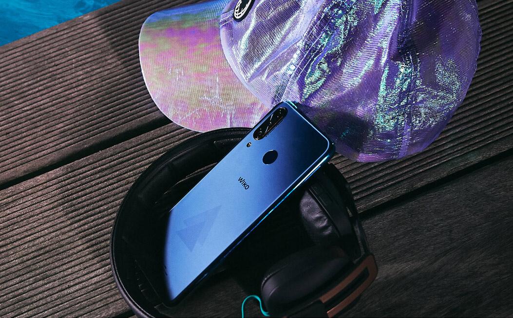 View3 range smartphone displayed next to a Wishake wireless headphone and a cap